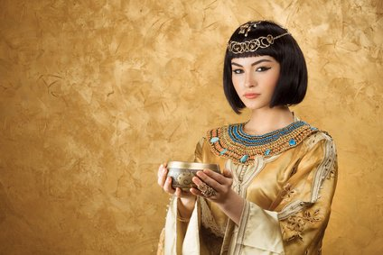 Beautiful woman like Egyptian Queen Cleopatra with cup on golden background
